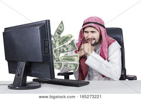 Picture of Arabian businessman feeling worried with money out of his computer isolated on white background
