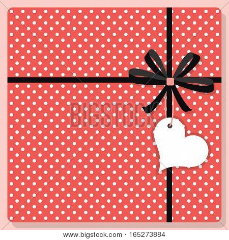 Cute trendy pink and white polka dots pattern gift from top view with bow and hanging heart shape tag