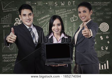 Group of business people showing blank screen on laptop and thumbs up