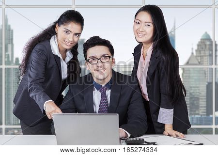 Group of multi ethnic businesspeople discussing with laptop in office and smiling on the camera