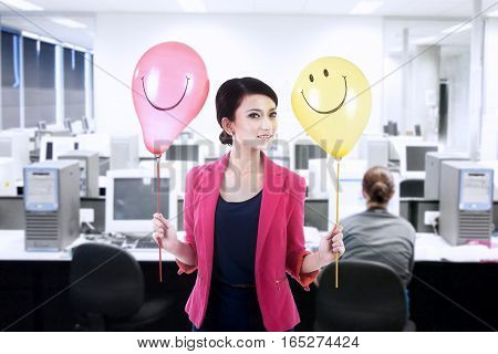 Beautiful businesswoman holding happy balloons at office