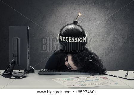 Young businesswoman sleeping on the desk with bomb recession over her head