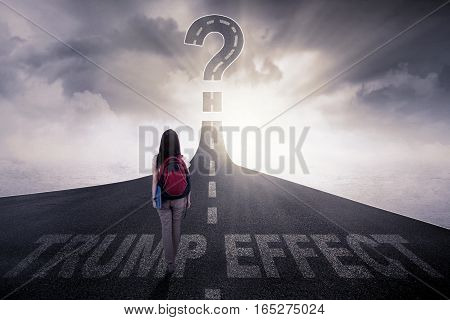 Rear view of a female college student walking on the highway with a question mark and text of Trump Effect on the asphalt