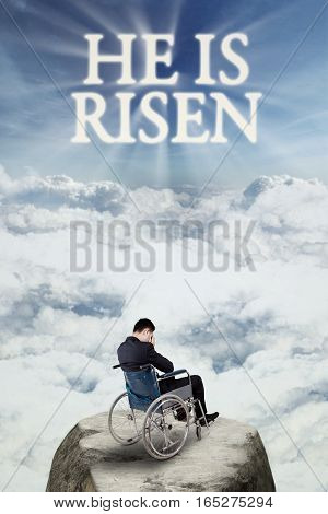 Image of disabled man sitting on wheelchair and looks sad at the cliff with text he is risen on the sky