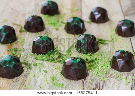 Pretty Chocolate candies on the wooden board