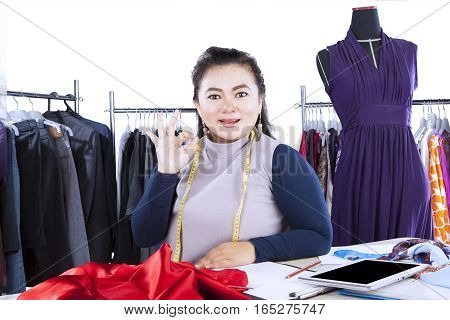 Portrait of fashion designer showing ok sign with her finger while looking at the camera isolated on white background