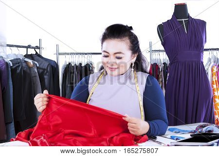 Female fashion designer working at workplace and looking at a red textile material with clothes hanger on the background