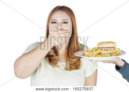 Portrait of fat woman closed her mouth while refusing hamburger and french fries isolated on white background