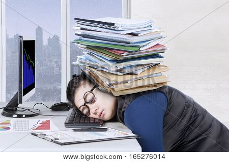 Female entrepreneur feels tired with pile of documents over head while sleeps on the desk winter background on the window