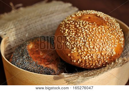buns with sesame and poppy seeds in burlap basket.