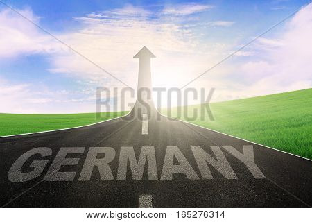 Empty road with word of Germany and arrow upward at the end of a road