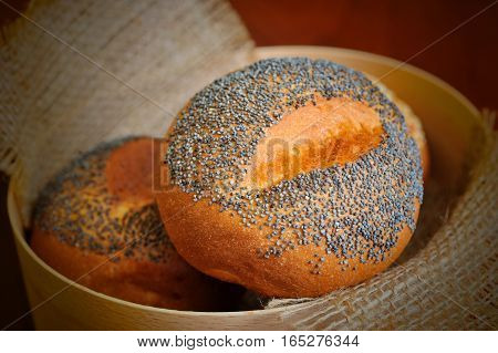 buns with sesame and poppy seeds in basket with burlap