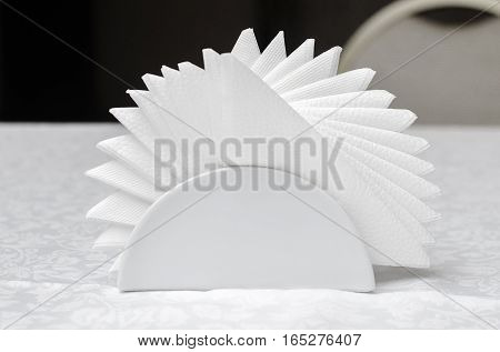 Paper napkins folded like a fan in a glass stand on a table with a white tablecloth