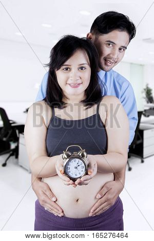 Portrait of happy couple waiting childbirth with clock in hands