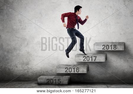 Picture of male entrepreneur jumping on the stairs with number 2017 toward 2018