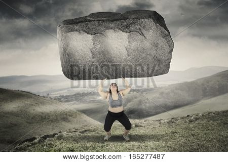 Picture of obese woman lifting a big stone while standing in hills