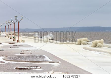 Winter storm on the lake and city embankment covered with ice. Onega lake, Petrozavodsk, Russia