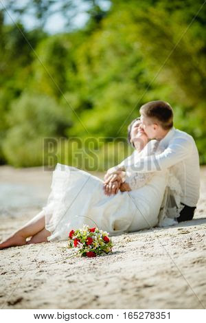 The bride with the groom in white sitting on the beach.