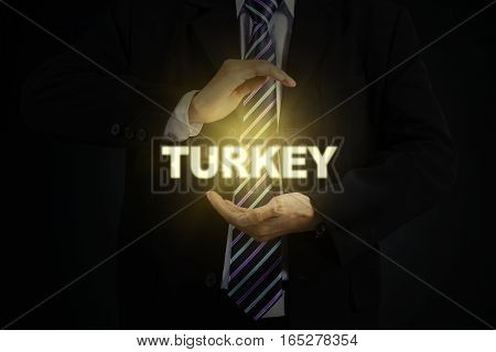 Close up of male entrepreneur wearing formal suit and protecting a Turkey word