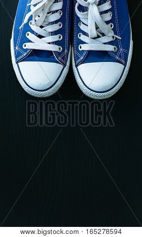 Blue textile youth sneakers on a black wooden surface top view an empty space