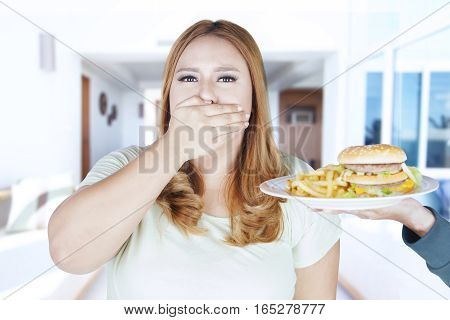 Portrait of young woman closed her mouth while refusing hamburger and french fries on plate