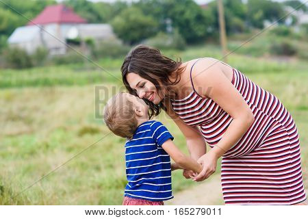 Pregnant woman kissing her son. Pregnant woman walking countryside with her son.