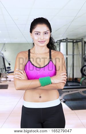 Portrait of young woman posing and folded hands while standing in fitness center