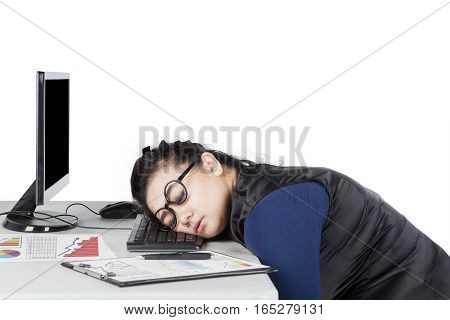 Portrait of young woman sleeping on the keyboard with financial chart on the desk isolated on white background