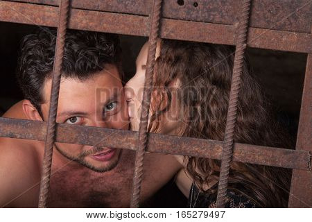 Young couple kissing behind a lattice man and woman embrace and kiss on lips of the rusty iron bars