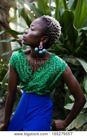 Beautiful black woman with glossy makeup. Stylish young african american teenage girl posing in fashion clothes.African-american fashion style. Beautiful African woman wearing color dress and bijou