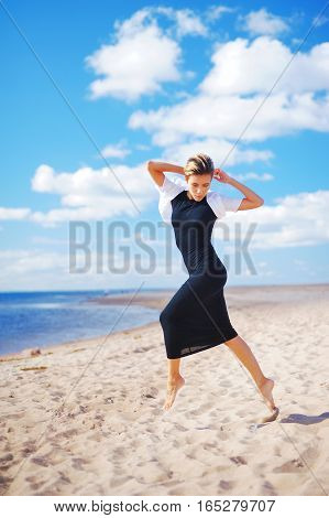 Young slim woman dancing barefoot on the sandy shores on the background beautiful white clouds on blue sky.