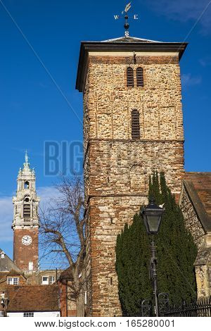 A view of the old Saxon tower of the Holy Trinity church with the Victorian tower of Colchester Town Hall in the background in the historic town of Colchester Essex.