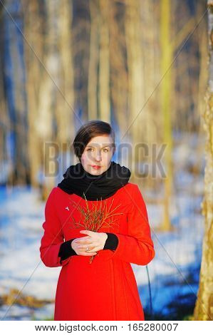 Portrait of beautiful young woman in winter mystical forest with a green twig in the hands