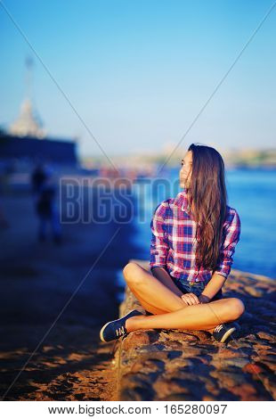 Portrait of young attractive girls long-haired brunette posing on the shore of Neva sitting near the water in a pose of a Lotus in rays of setting sun on background of St. Petersburg's landscape.