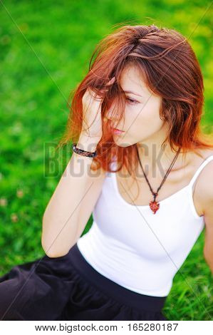 Portrait of cute long-haired girl sitting on the green lawn and looks to the side. Half of her face close hair she straightens her hairstyle with a hand
