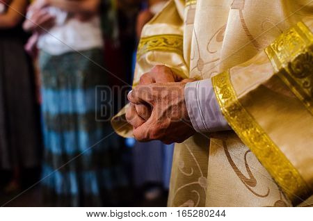 Hands of priest in the Christian church during the ceremony when the baptism