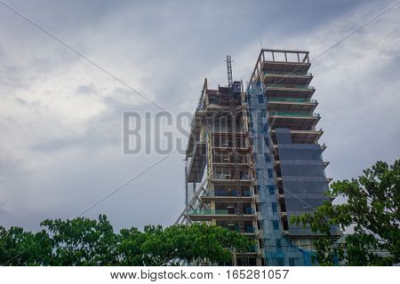 Building construction with cloudy sky as background and surrounding by trees photo taken in Jakarta Indonesia java