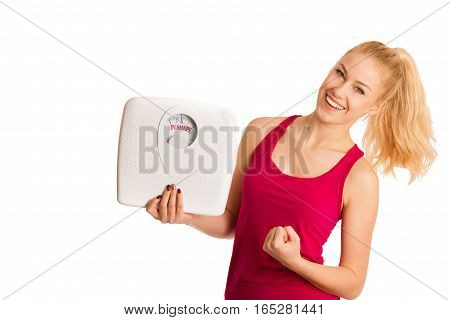 Happy Young Blond Woman Showing A Scale As She Has Perfect Shape And Weight