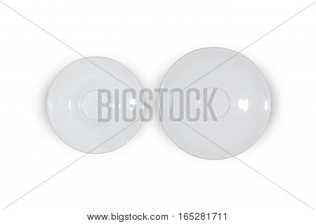 Two flat white saucers side by side smaller and bigger on white background directly from above