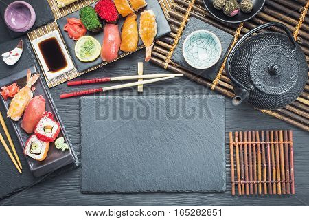 Asian style tableware with sushi set and tea  on black table,  top view