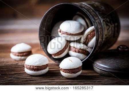 Macaroons With Nut Filling On Old Wooden Table