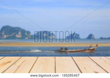 Wooden board empty table in front of blurred background. Perspective brown wood over sea with fisherman on boat for mock up display or montage your products vintage.