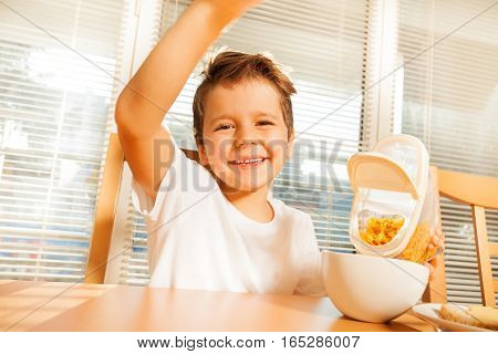 Happy little boy making breakfast, pouring corn flakes in a plate in the kitchen
