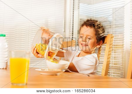Little boy pouring corn flakes in a plate making cereal breakfast in the kitchen