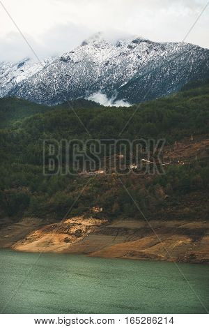 Green slopes of the Taurus mountains covered with snow and clouds and Dim Cay river valley in winter on gloomy day. Southern Turkey, Alanya
