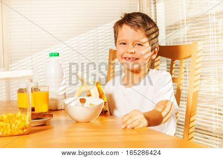 Smiling kid boy having healthy breakfast, holding banana in the kitchen