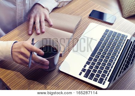 Businessman drinking coffee and working on laptop computer mobile phone writing business plan wearing white shirt