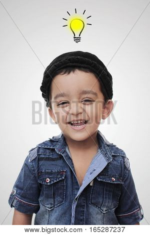 Portrait. happy little south asian boy wearing cultural hat. smiling and looking in the camera isolated on white