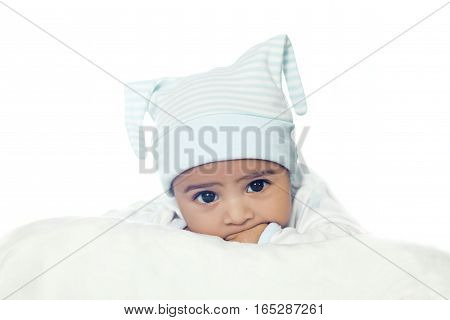 Adorable Six Month Baby Boy Wearing Blue Suite In White Bedding isolated on white