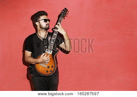 Closeup of one handsome passionate expressive cool young brunette rock musician men playing electric guitar standing against red background